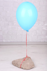 Color balloon with stone on grey wall background