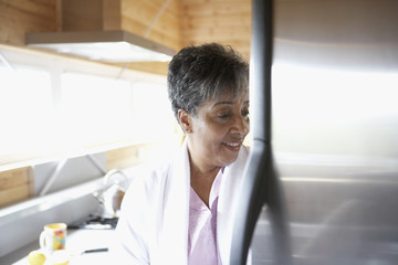 Senior African woman looking in refrigerator