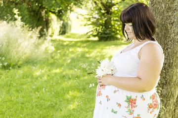 Werdende Mama schaut auf ihren Bauch