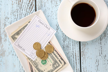 Check, money and cup of coffee on table close-up