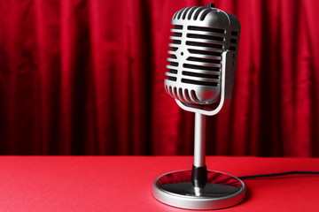 Vintage microphone on red cloth background