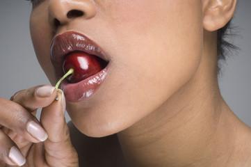 African woman eating cherry
