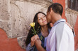 Hispanic couple kissing with rose