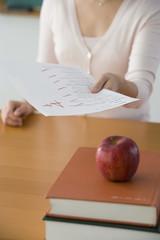 Asian female teacher handing back paper