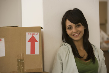 Woman sitting next to moving box