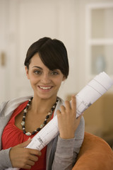 Young woman holding blueprints