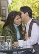 Hispanic man telling secret to girlfriend