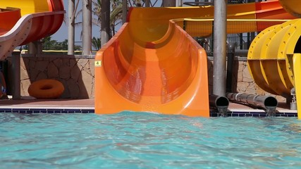 Little girl sliding down on water slide in water park