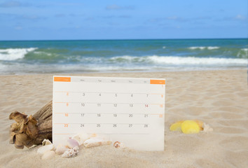 Sea shells and calendor pad on white sand beach background colle
