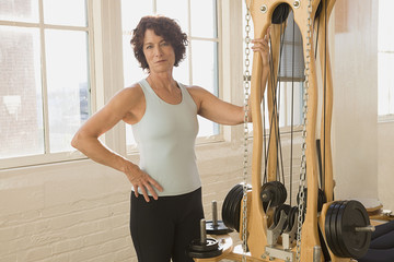 Senior woman standing next to exercise equipment