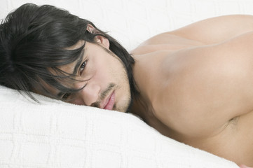 Young Hispanic laying on bed