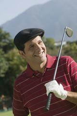 Hispanic man holding golf club over shoulder