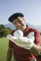 Hispanic man holding golf ball