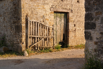 Entrance of a farm with a rickety gate in early morning light