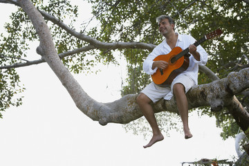 South American man playing guitar in tree