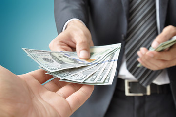 Hand receiving money from businessman - US dollar bills