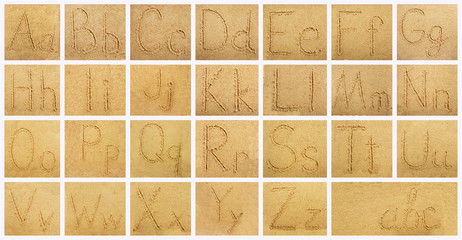 Handwritten alphabet letters on sand background