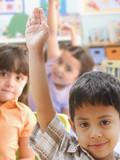Fototapety Hispanic boy raising hand in class