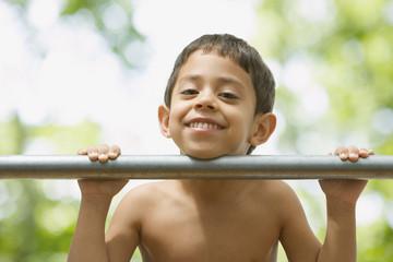 Hispanic boy leaning chin on bar