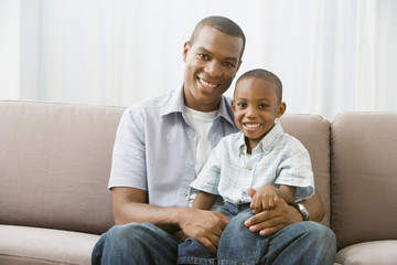 African American father and son on sofa