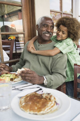 African American boy hugging grandfather