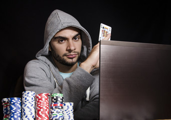 Online poker player holding king of spades