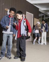 Multi-ethnic school children listening to mp3 players