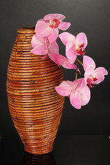 Bamboo vase with orchid on grey background