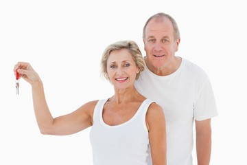 Mature couple smiling at camera with new house key