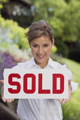 Hispanic woman holding Sold sign
