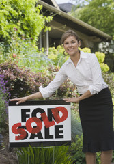 Hispanic woman next to Sold sign