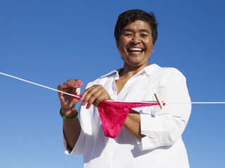 Mixed Race woman hanging underwear on line