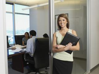 Hispanic businesswoman next to conference room