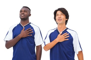Football players in blue with hands on heart