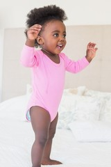Baby girl in pink babygro standing on bed