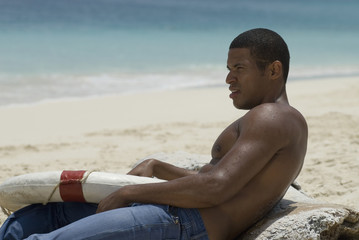 Hispanic man holding life preserver at beach