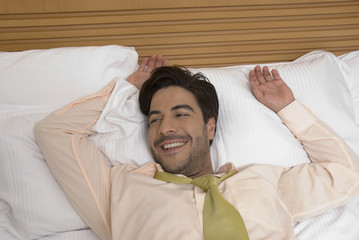 Hispanic businessman laying in bed