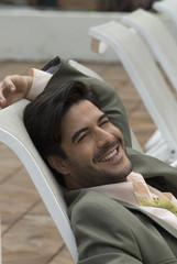 Hispanic businessman sitting in lounge chair