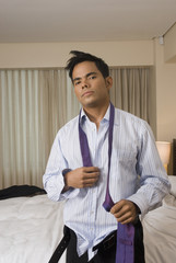 Hispanic businessman getting dressed