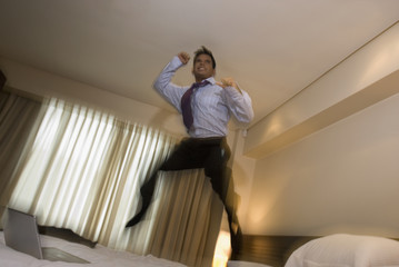 Hispanic businessman jumping on bed