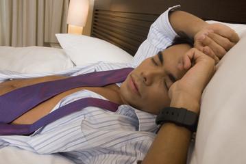 Hispanic businessman sleeping on bed