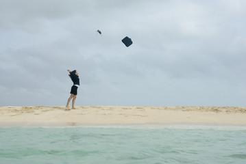 Hispanic businesswoman throwing briefcase in air