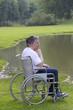 symbole de la solitude- homme en fauteuil  roulant face a un lac