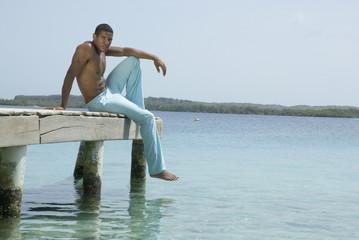 Hispanic man sitting on dock