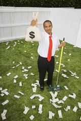 Mixed Race businessman raking up money