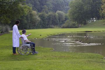 infirmier accompagnant  un homme en fauteuil roulant dans un par