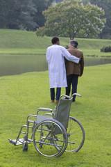 iRéeducation-infirmier aidant patient en fauteuil roulant