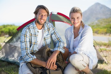 Attractive hiking couple smiling at camera outside their tent