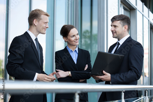 Business people talking in front of office building