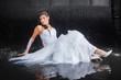 Bride sitting under rain